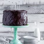 Three-layer chocolate birthday cake with chocolate cream cheese frosting on a green glass cake stand.