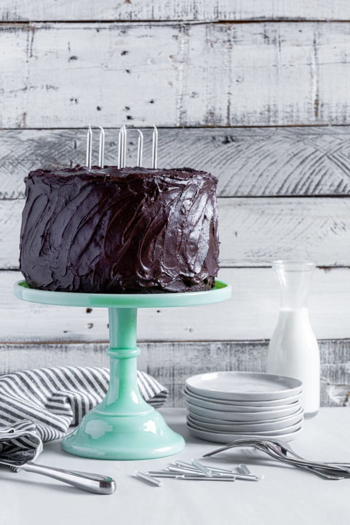Three-layer chocolate birthday cake with chocolate cream cheese frosting on green glass cake stand.