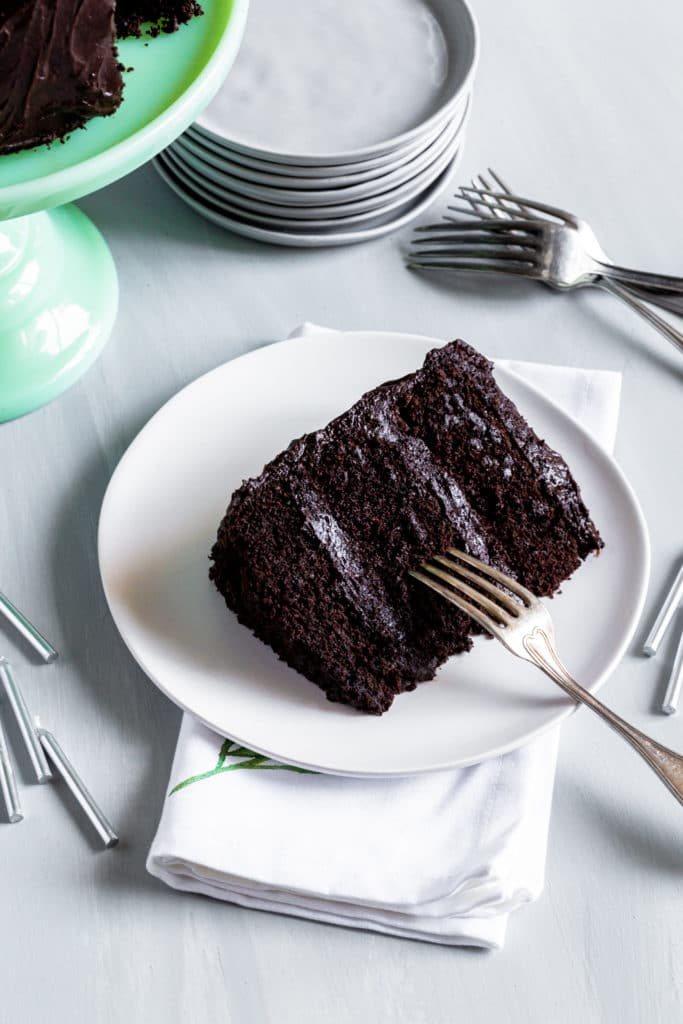 Piece of super moist chocolate cake on a white plate with silver fork and birthday candles.