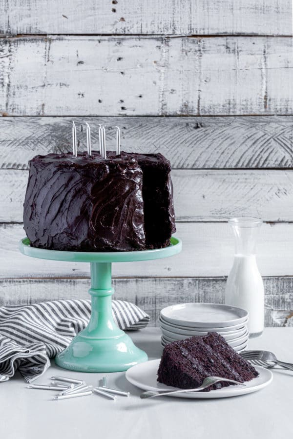 Chocolate birthday cake with candles on a green depression-glass cake stand next to slice of Matilda cake.