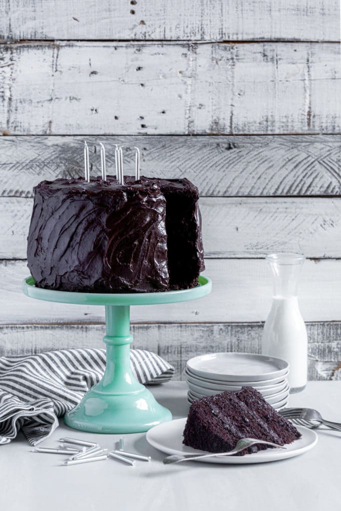 Chocolate birthday cake with candles on a green cake stand by a slice of Matilda cake.