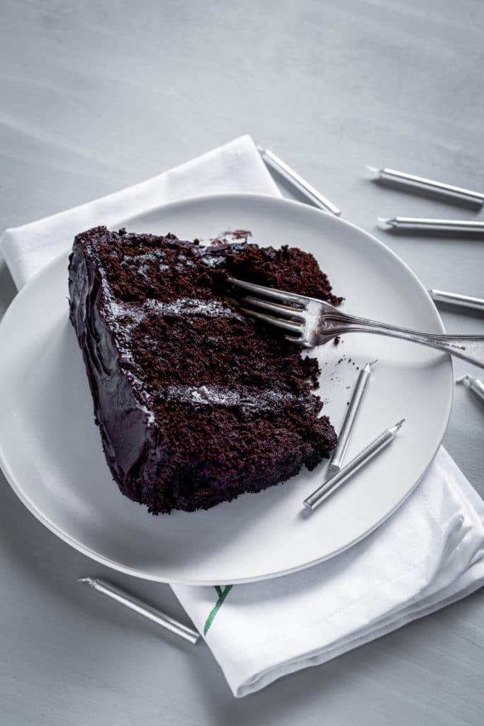 Slice of chocolate cake with silver candles and a metal fork.