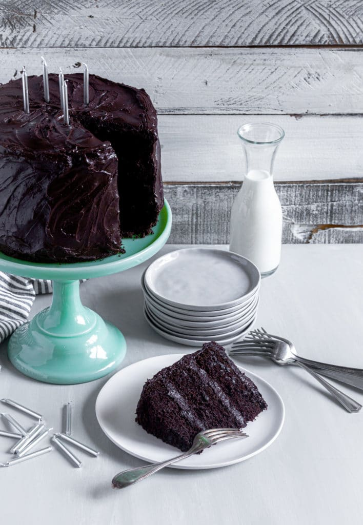 Matilda chocolate cake on a green cake stand with a slice of birthday cake and silver candles.