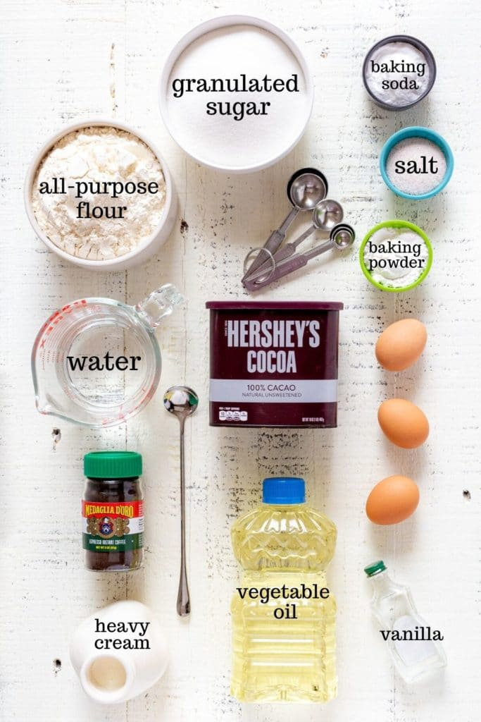 Ingredients for chocolate Matilda cake laid out on a white rustic tabletop.