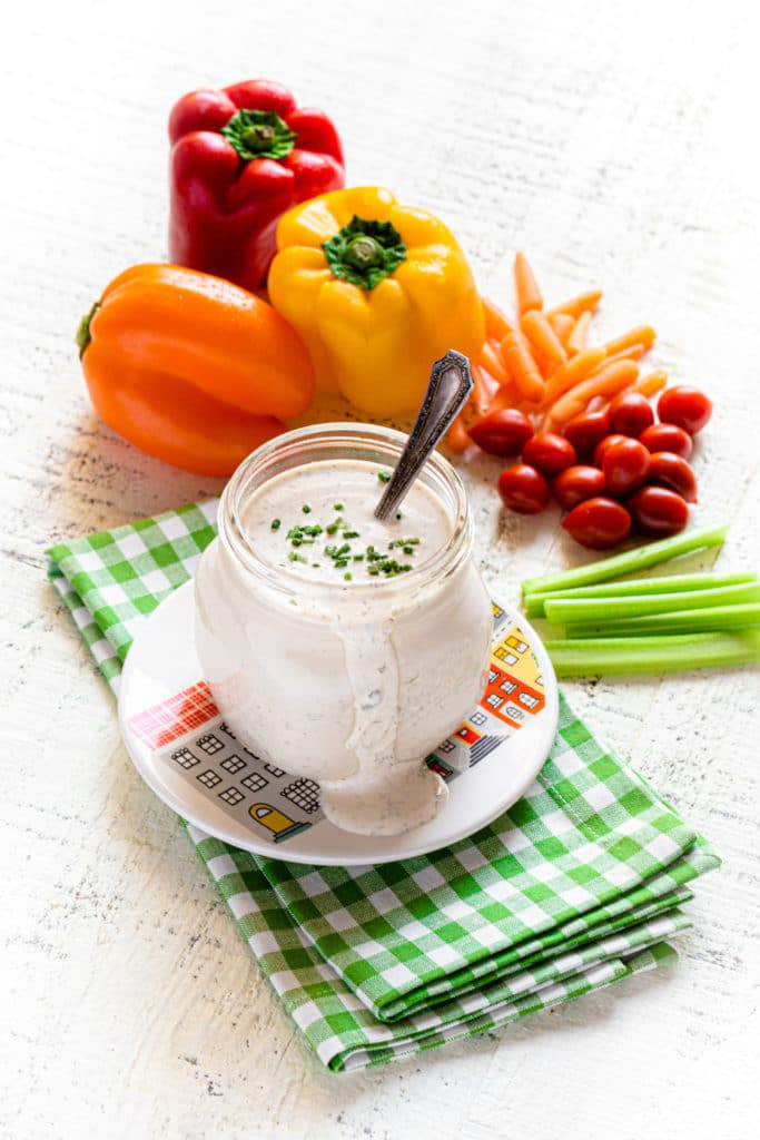 Homemade buttermilk ranch dressing in a mason jar surrounded by fresh veggies for dipping.