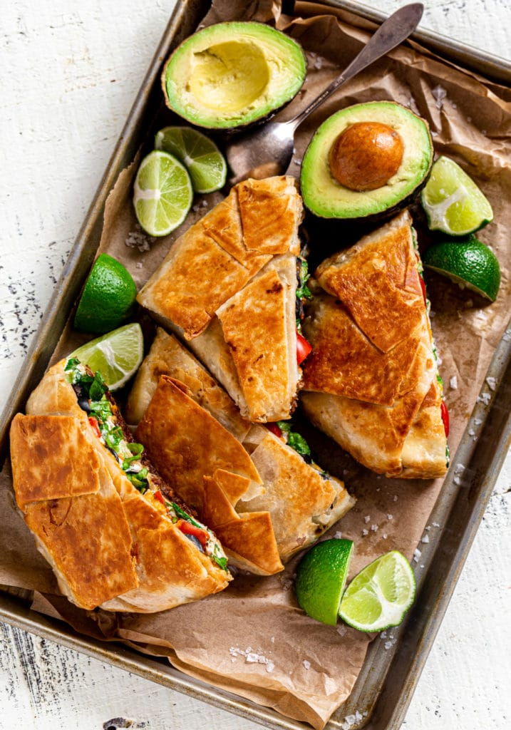 Overhead view: Crunchwrap supreme on parchment-lined metal tray with wedges of lime and avocado.