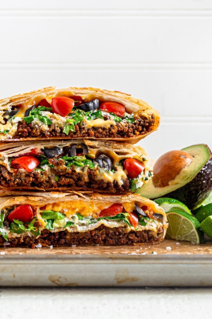 Homemade crunchwrap supreme cut in half and stacked on metal serving tray.