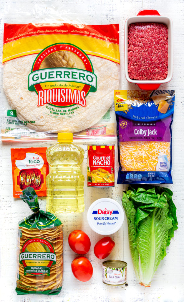 Ingredients for making a crunchwrap supreme laid out on a rustic white tabletop.