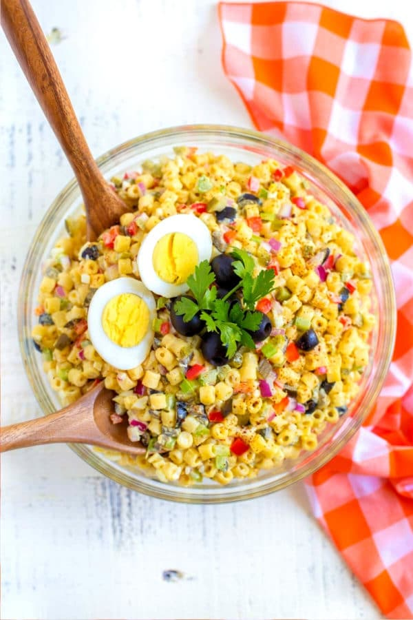 Grandma's classic macaroni salad recipe served in a glass bowl with wooden salad servers.