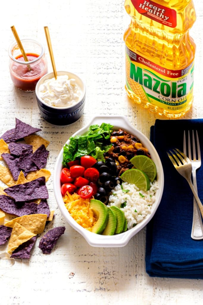 A healthy burrito bowl with multi-color tortilla chips, condiments, deep-blue napkin and forks.