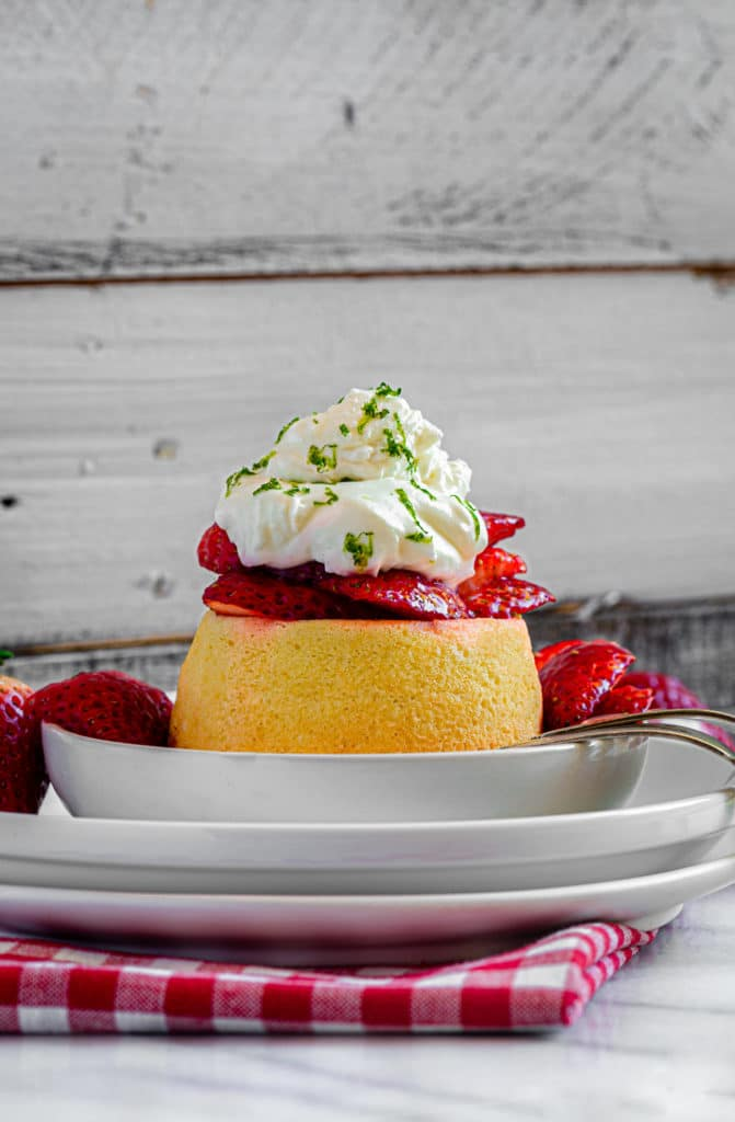 Strawberry shortcake dessert on a small plate with fork and gingham red/white napkin.
