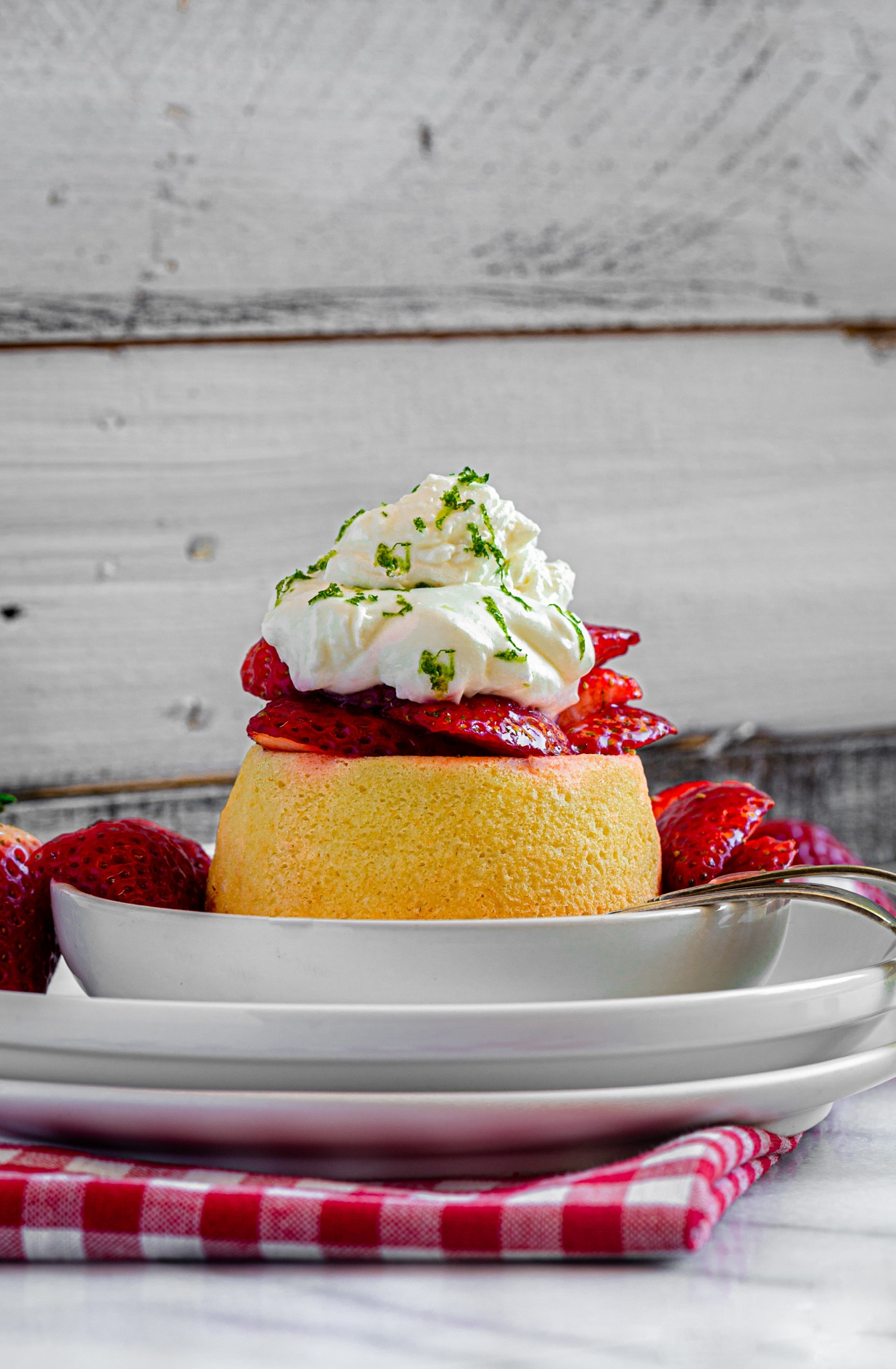 Strawberry shortcake dessert on a small plate with fork and napkin.