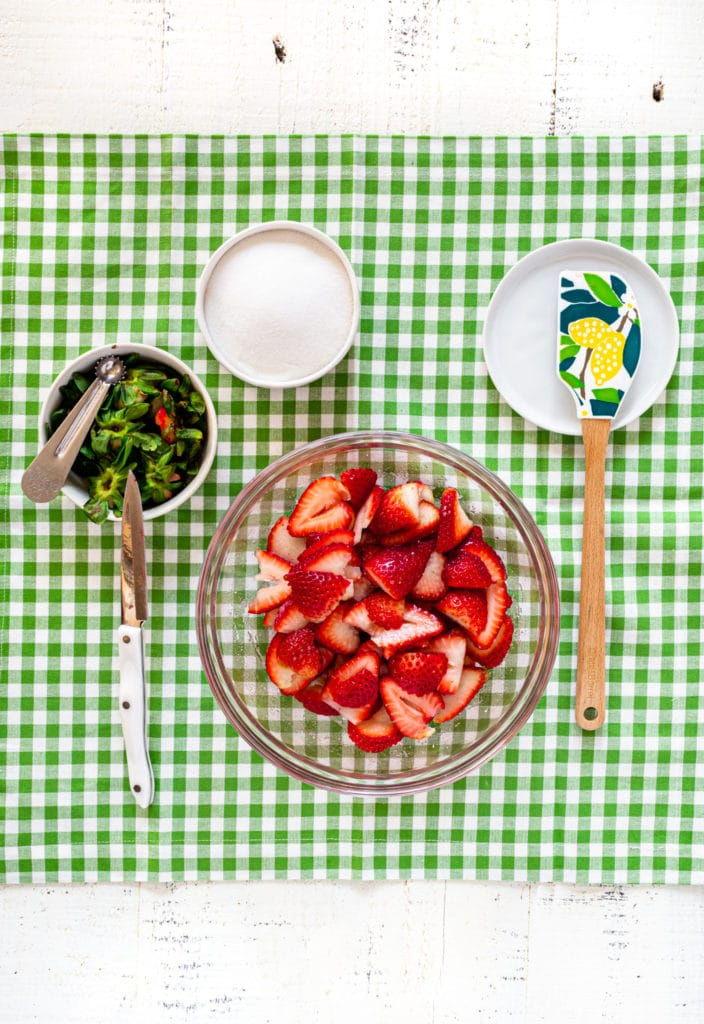 Strawberry shortcake filling: hulled and sliced strawberries in a bowl plus granulated sugar.