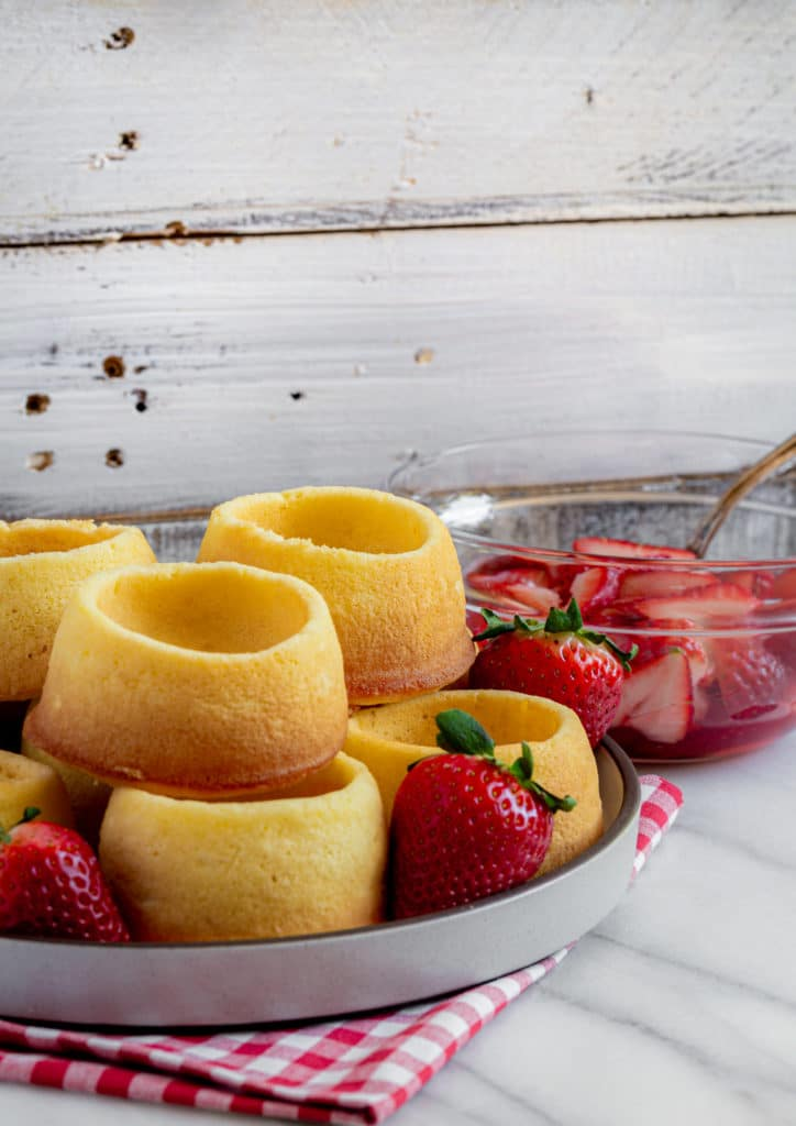 A batch of freshly-baked strawberry shortcake cups on a plate next to strawberries.