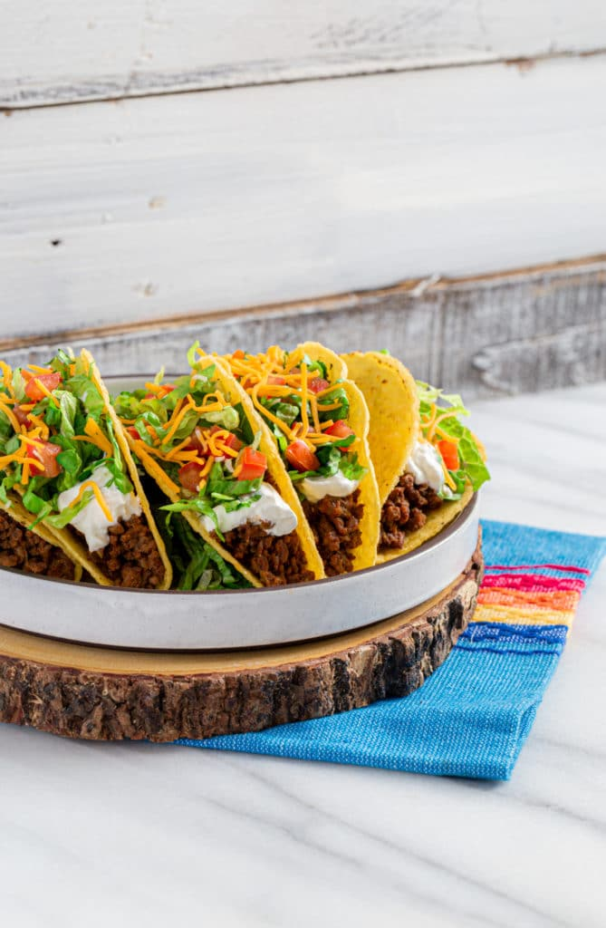 Five Crunchy Ground Beef Tacos on a serving plate. This is a DIY Taco Bell recipe.