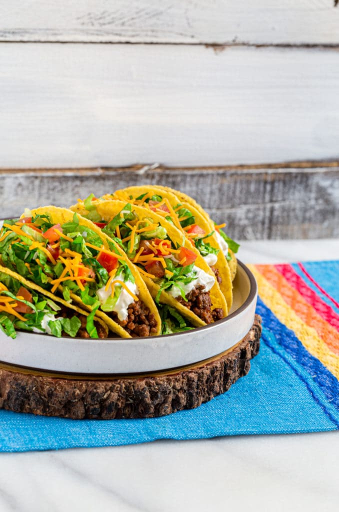 Four ground beef tacos on a platter made with a DIY Taco Bell meat recipe.
