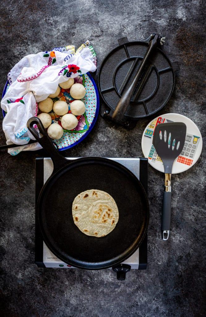 Cooking homemade corn tortillas on a cast-iron comal.