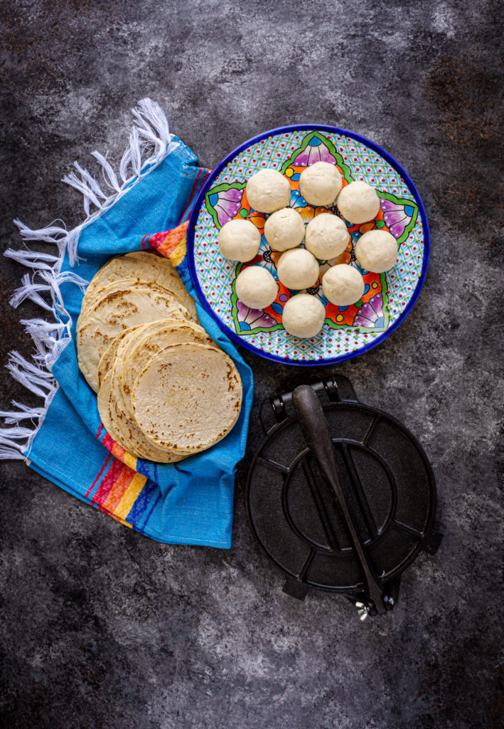 Balls of masa on a Mexican clay plate next to homemade corn tortillas and a comal.