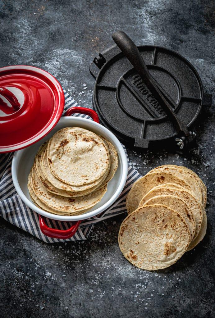 Homemade corn tortillas in a red tortilla warmer next to a cast-iron press.