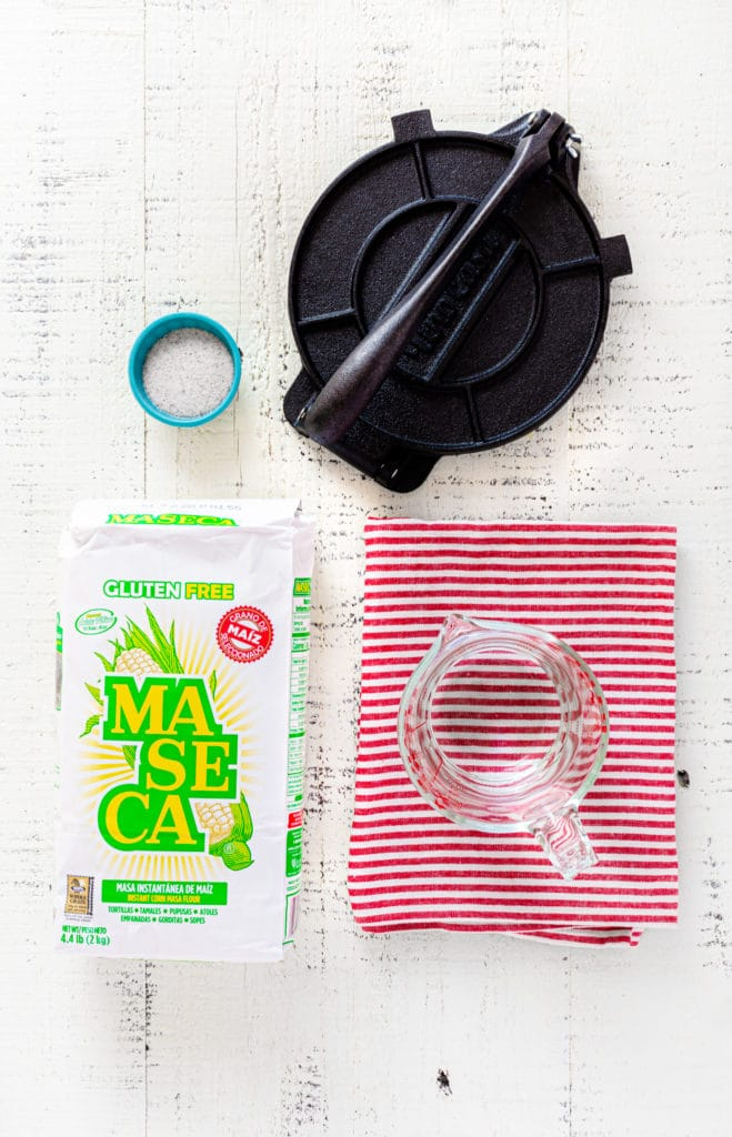 Ingredients for homemade corn tortilla recipe along with a cast-iron tortilla press.