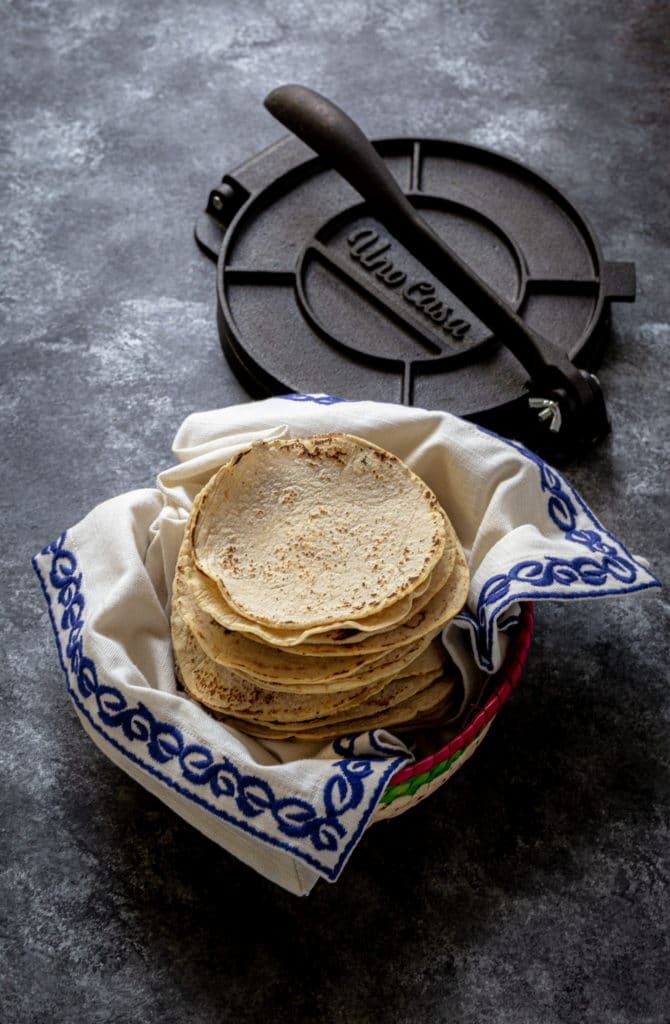 Mexican tortilla basket with a stack of freshly-made corn tortillas and a metal tortilla press.