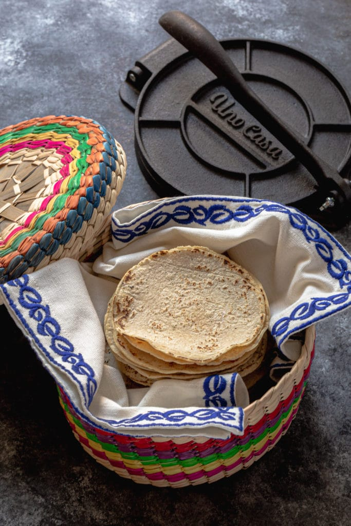 Traditional Mexican tortilla warmer filled with a stack of homemade corn tortillas fresh off the comal.