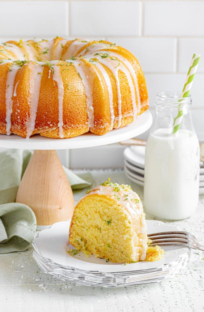 Lemon bundt cake on a stand next to a slice of Starbucks lemon loaf and milk.