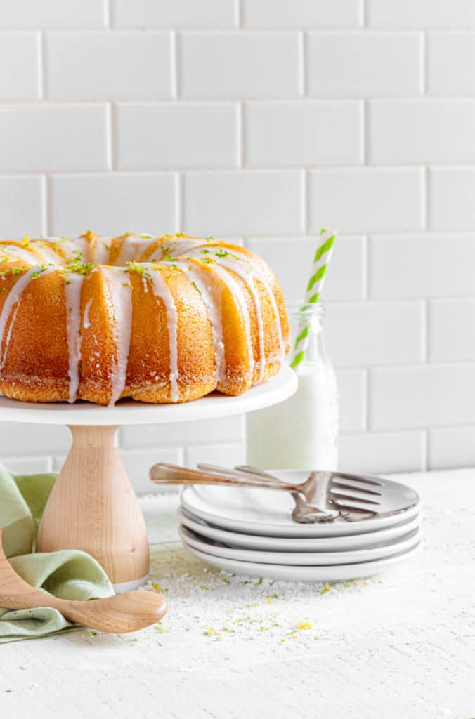 Lemon Bundt Cake on a stand with dessert plates and forks.