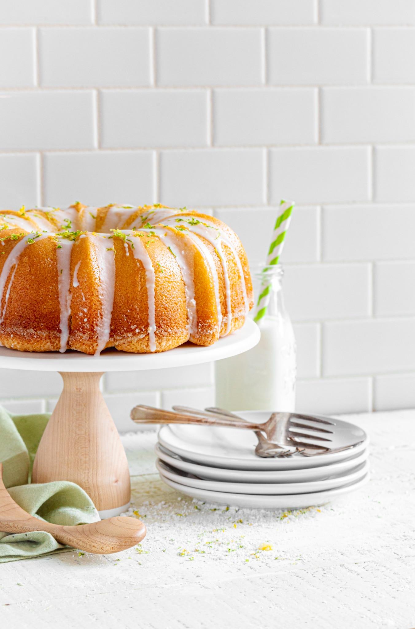 Lemon Bundt Cake on a stand with dessert plates and forks.