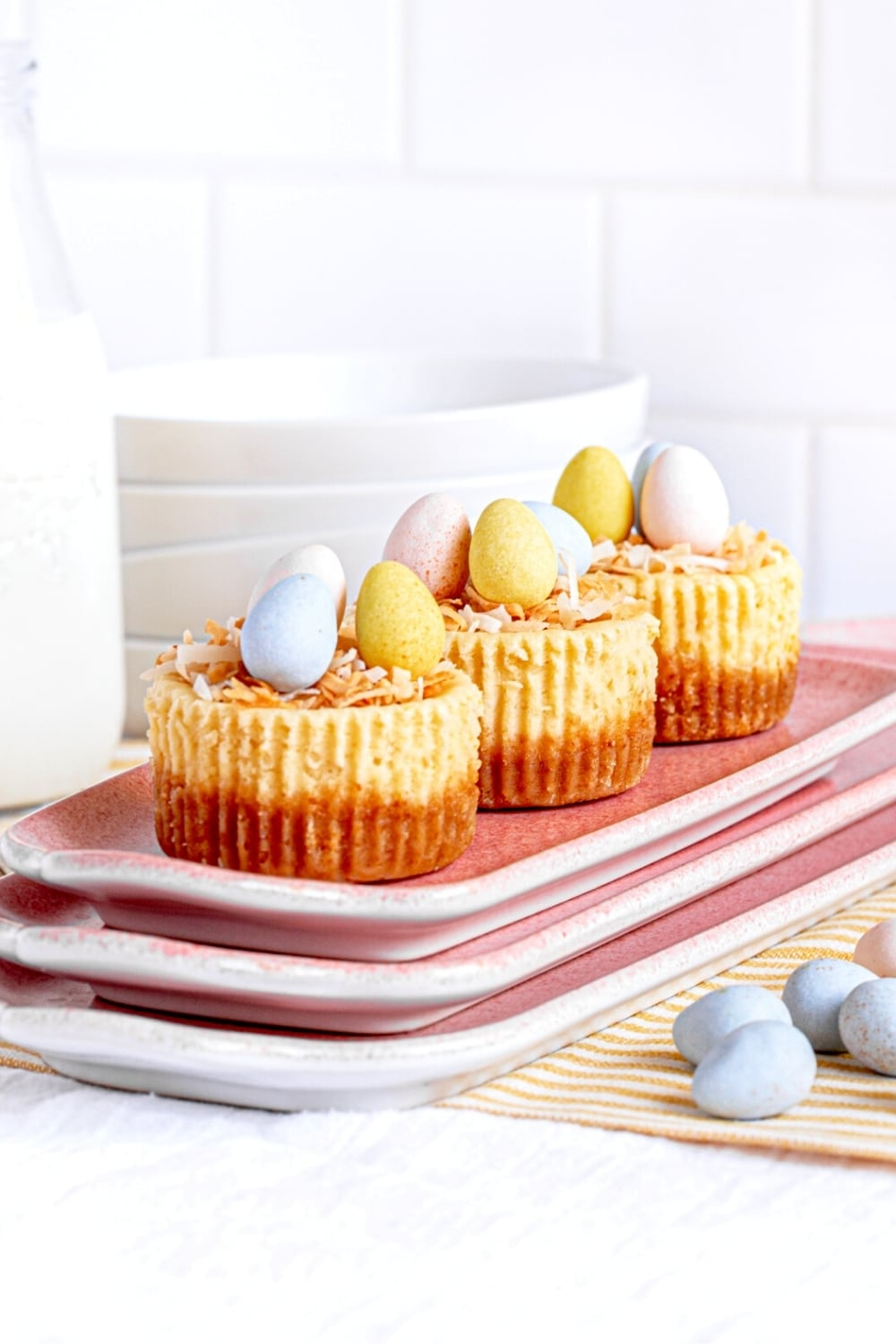 Mini Easter cheesecakes with a bird's nest of shredded coconut with candy eggs on a pink platter.