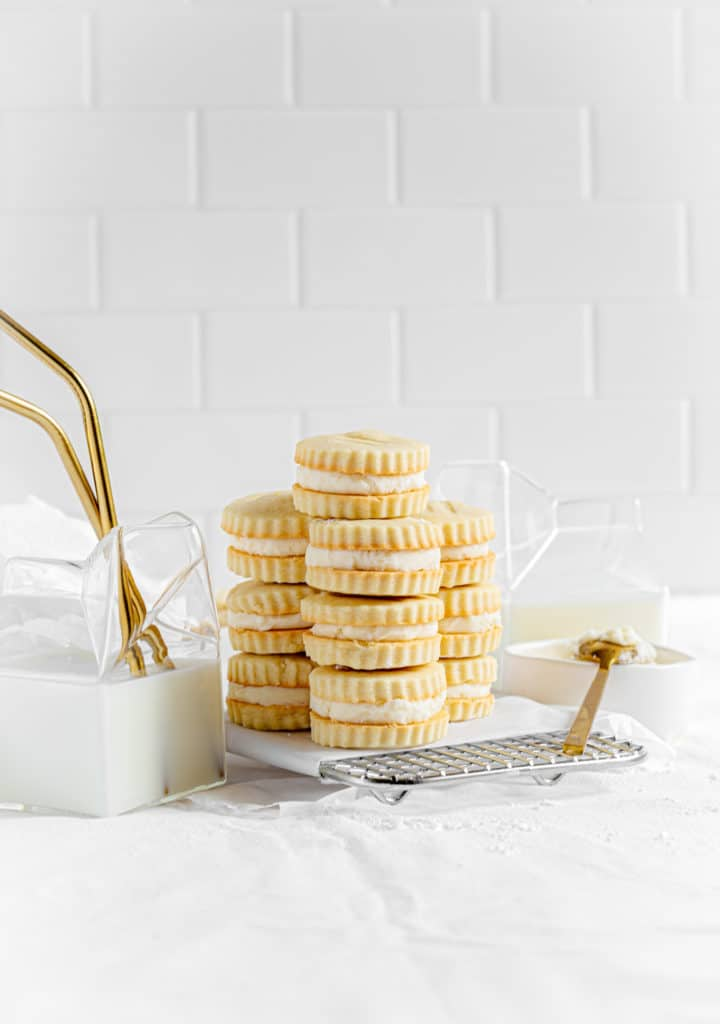 Three stacks of vanilla creme sandwich cookies on a metal cooling tray next to glass containers of milk.