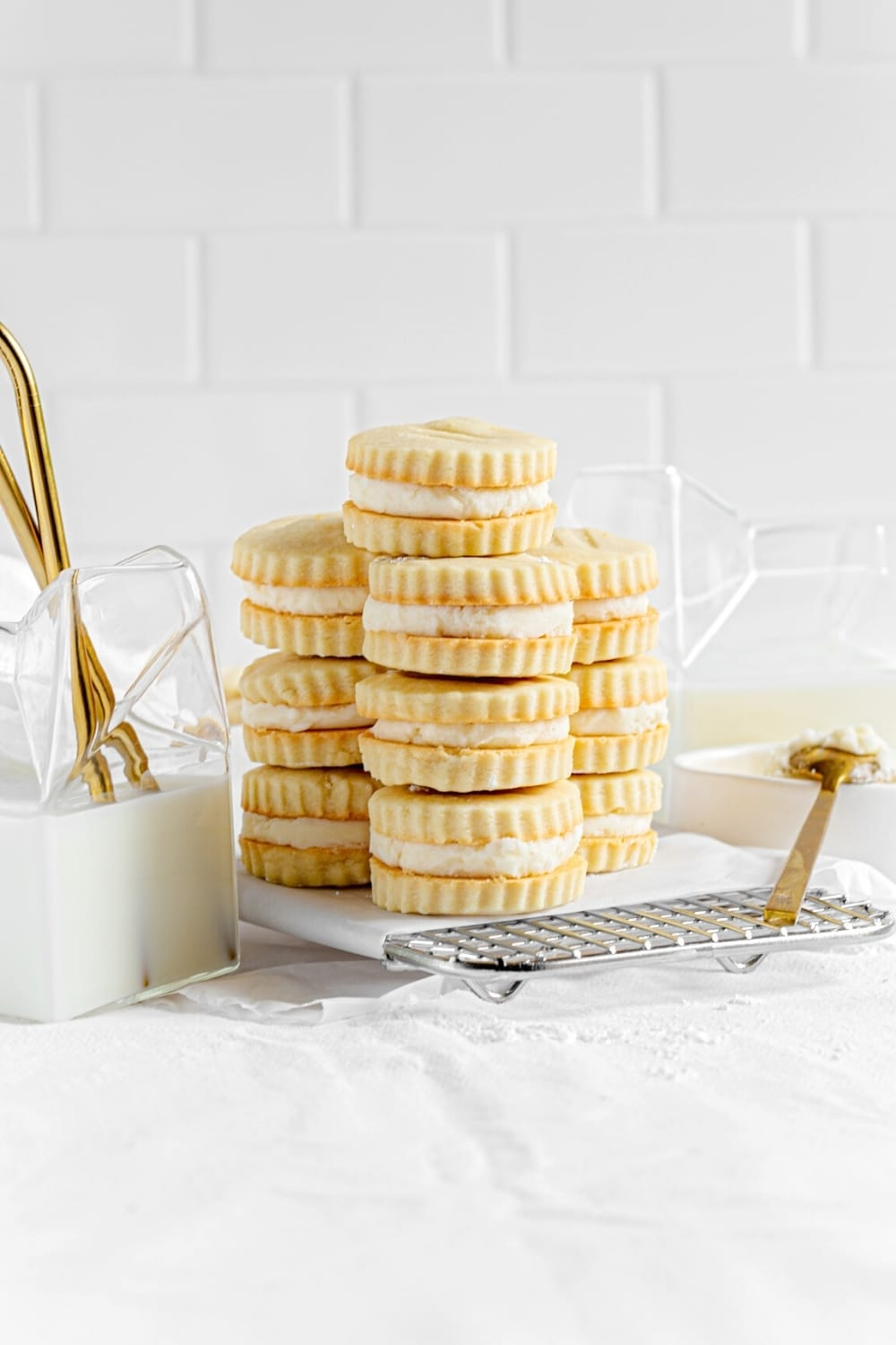 Three stacks of vanilla creme cookies on a metal cooling rack next to glass containers of milk.