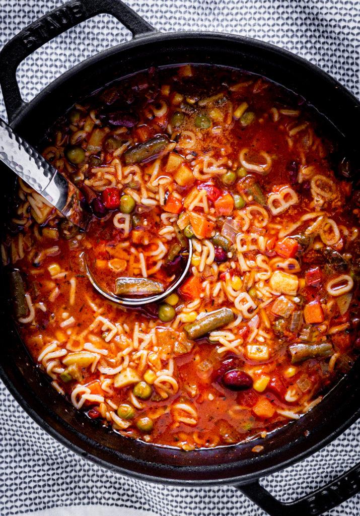 Alphabet soup (sopa de letras) in a black Dutch oven with a silver soup ladle.