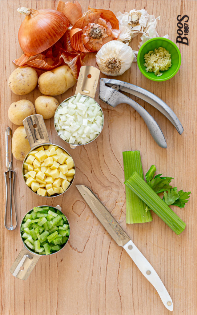 RECIPE PREP FOR VEGETABLE SOUP: Onion, garlic, potatoes, celery on a wooden cutting board with knife.