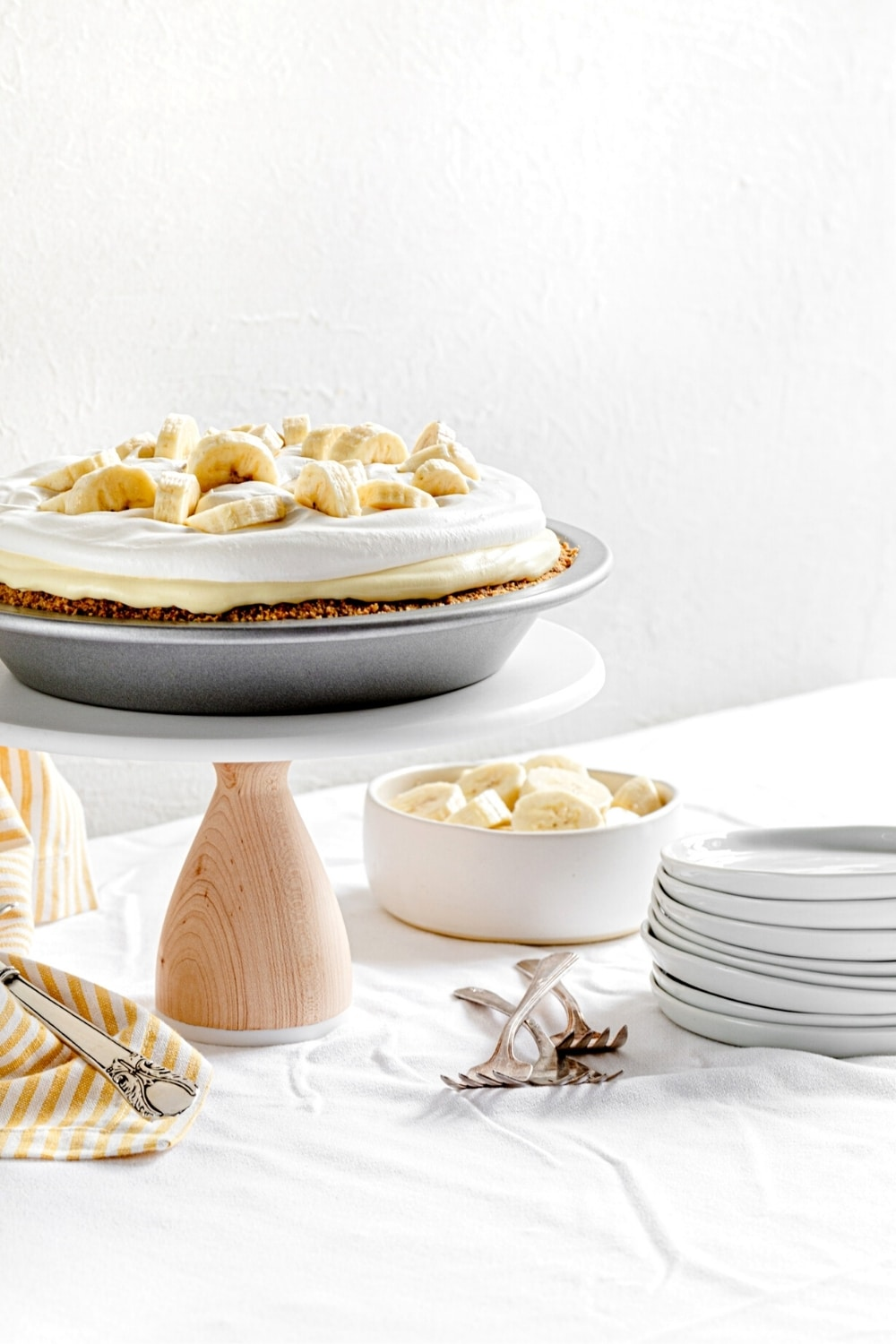 Banana pudding pie (AKA: Banana cream pie) on a dessert stand with plates and forks.