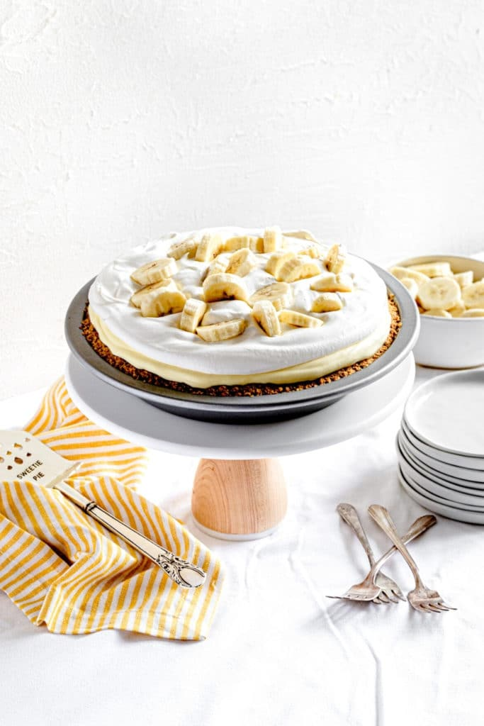 Banana Pudding Pie on a dessert stand with a metal server, plates and forks.