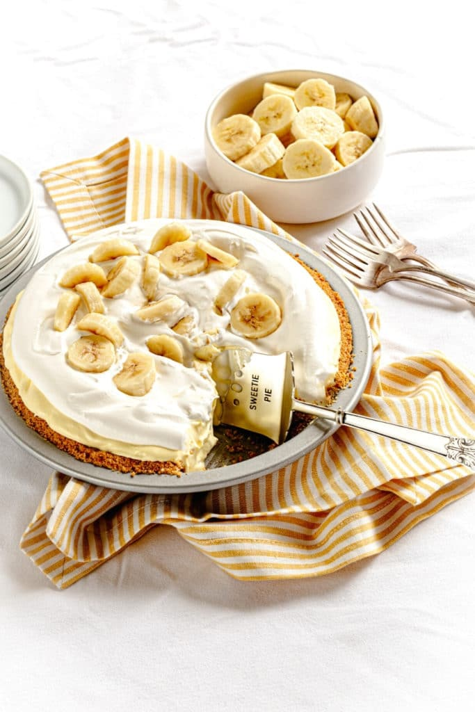 Banana Pudding Pie in metal pie pan with pie server, and forks on a white tabletop.