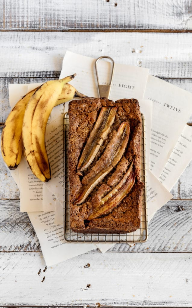 Loaf of banana walnut bread cooling on a wire rack next to 2 ripe bananas.