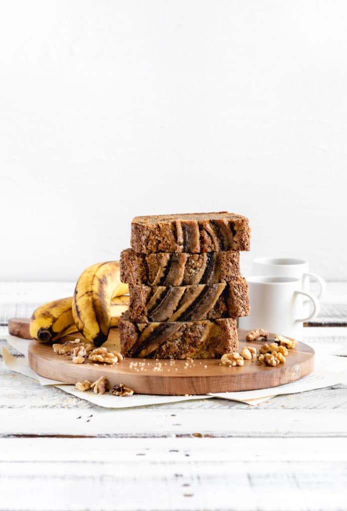 Stack of 4 slices of banana walnut bread on a wooden board with small coffee cups.