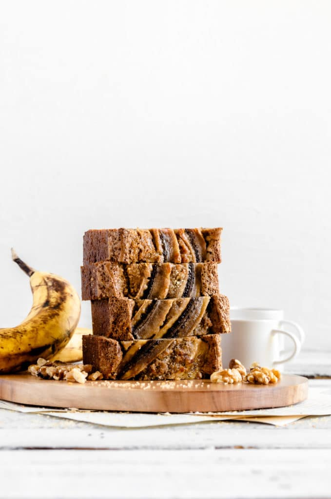 Four slices of banana bread with nuts on a wooden board (Starbucks banana bread recipe).