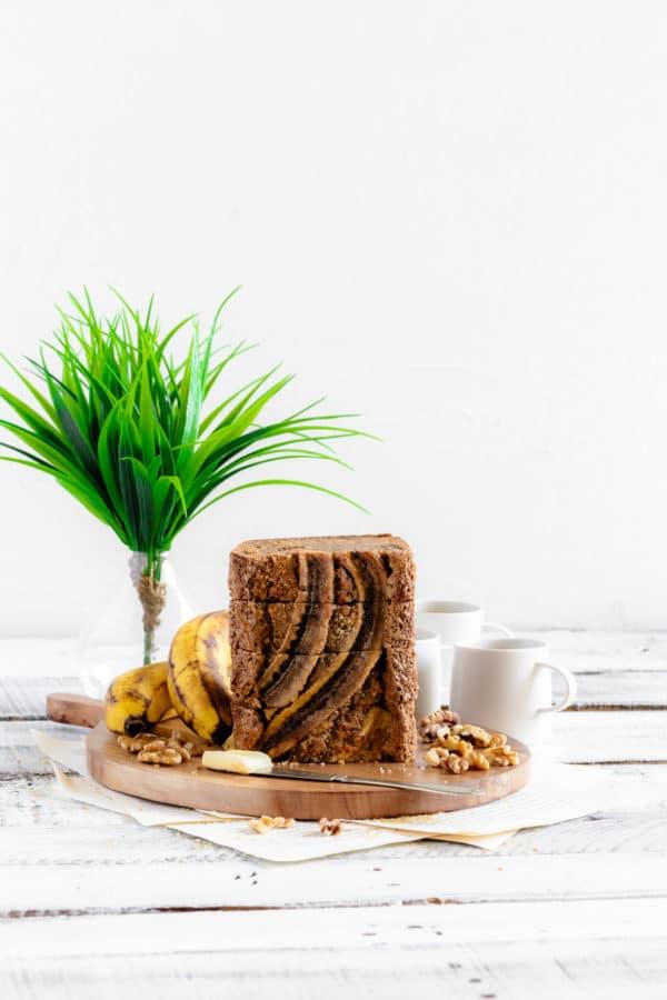 Slices of banana walnut bread from Starbucks banana bread recipe stacked on a wooden board.