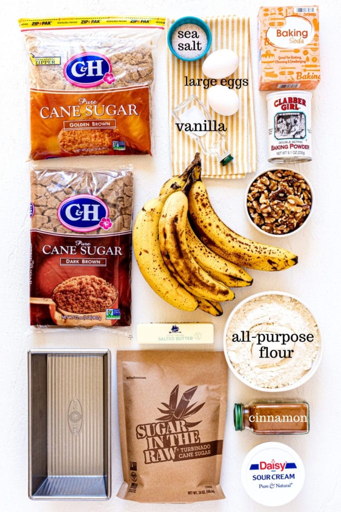 Ingredients for banana walnut bread recipe on a white tabletop with a 9x5-inch loaf pan.