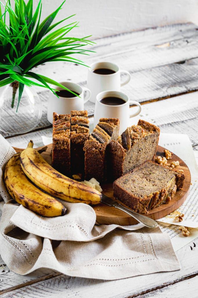 Outdoor breakfast table with banana walnut bread on a wooden board served with coffee.