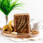Best ever banana bread with walnuts sliced on a wooden board.