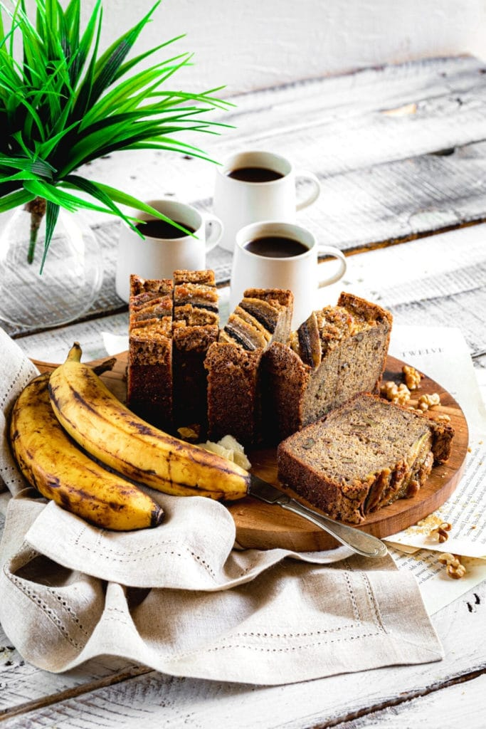 Outdoor breakfast table with banana walnut bread on a wooden board with cups of coffee.