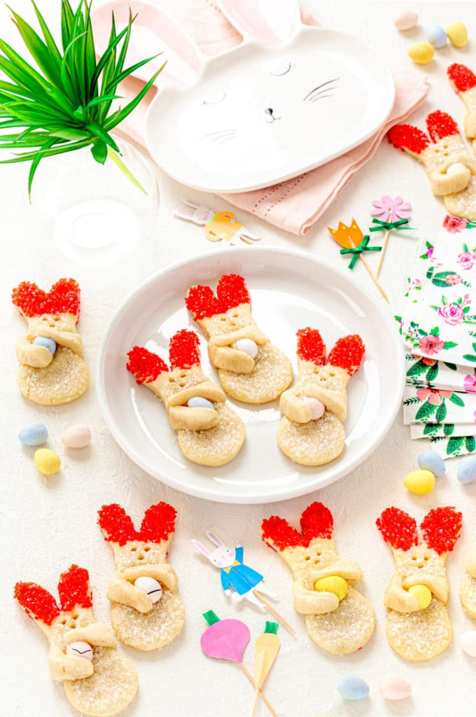 Easter bunny cookies on an Easter brunch table with spring napkins and ceramic bunny plate.
