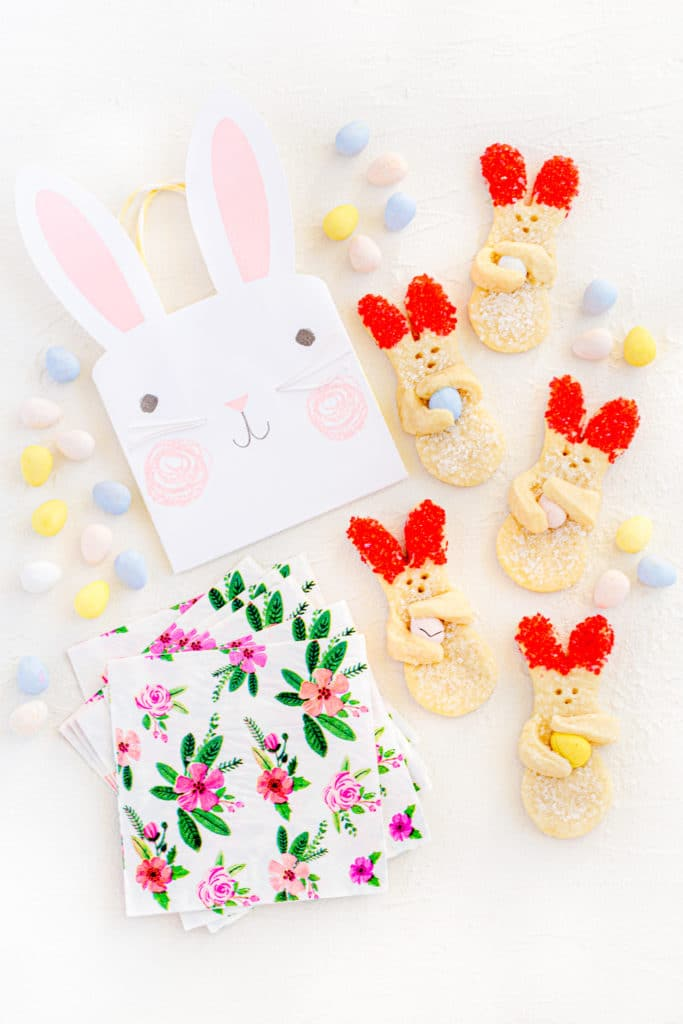 Easter bunny cookies on a white tabletop with spring dessert napkins and small handled bunny bag.