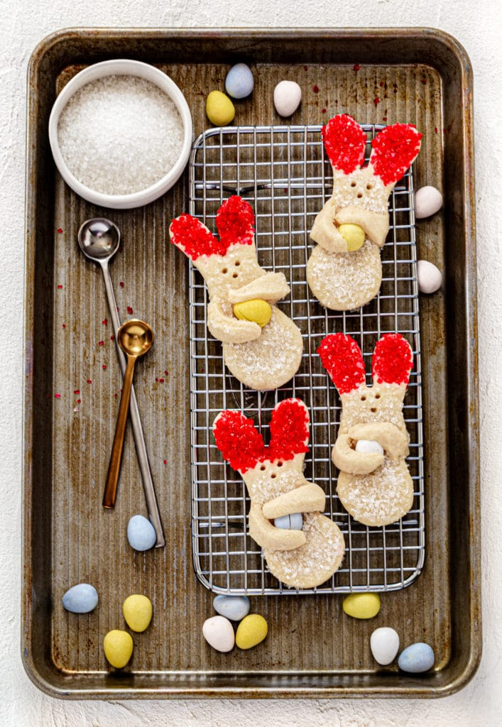 Bunny cookies (decorated Easter sugar cookies) on a baking tray with sugar crystals and candy eggs.