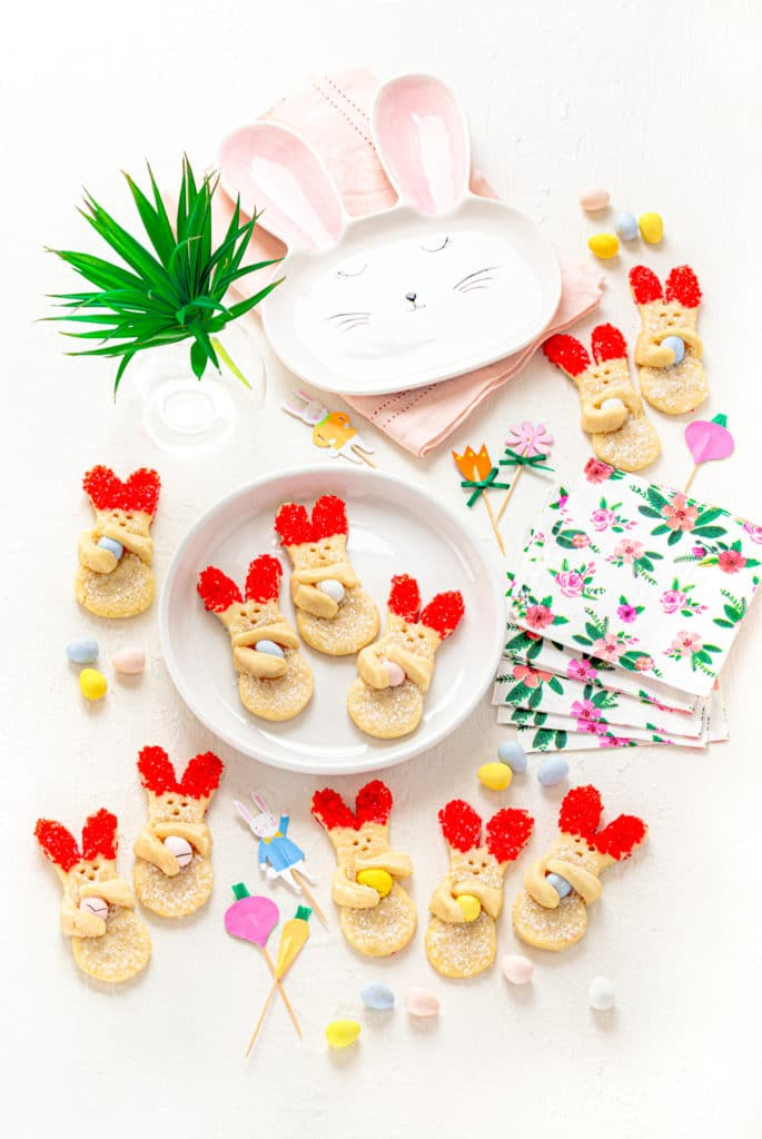 Bunny cookies (Easter Sugar Cookies) on a white tabletop with napkins, green plant and bunny plate.