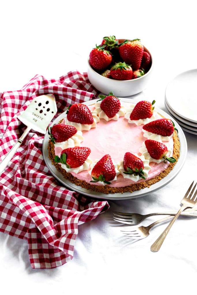 Strawberry Jello Cool Whip Pie on a graham cracker crust garnished with whipped cream and strawberries.